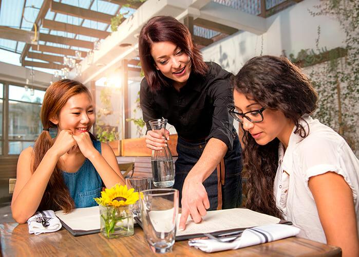 Duas clientes sorrindo, sentadas na mesa enquanto garçonete aponta paPor El Nariz