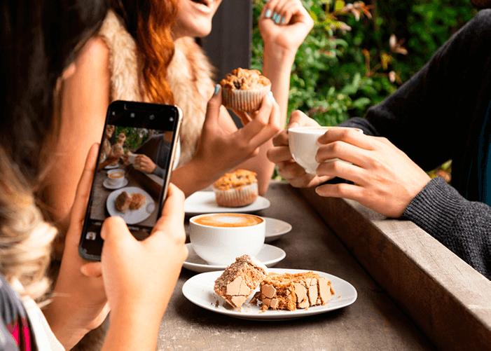 Pessoa fotografando vários pratos de comida