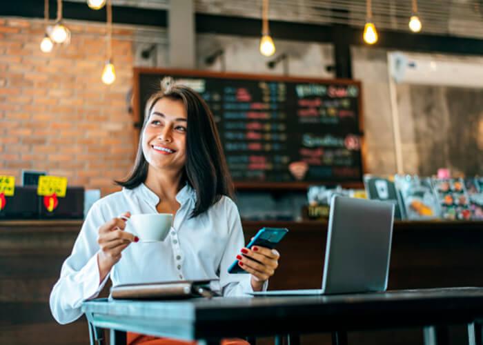 Mulher sentada alegre em uma cafeteria.