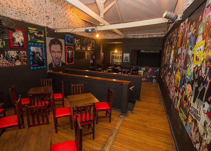 Bar interno com parede forrada de personagens de seriados, mesas de madeira quadradas com cadeiras