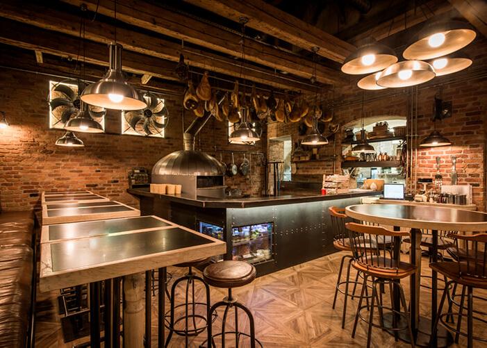 bar com mesas de madeira e balcão preto