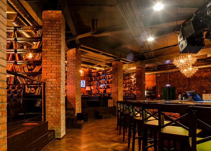 Bar amplo com vigas de tijolinhos a vista, parede de tijos aparente. Cadeiras de madeira