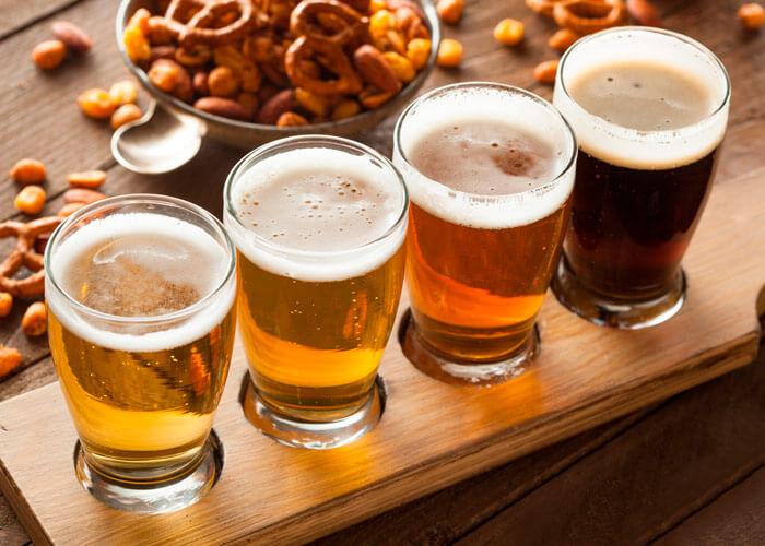 4 copos iguais com cervejas diferentes dentro em cima da tábua de madeira