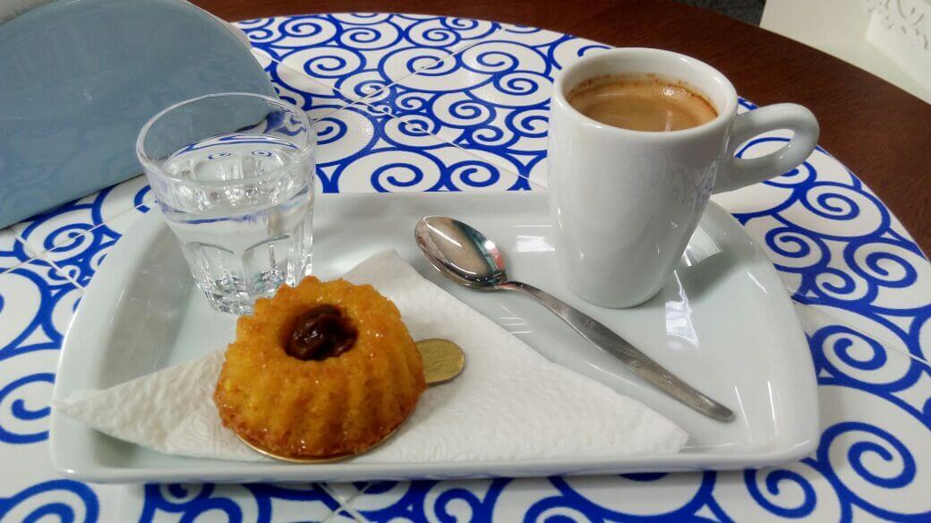 Prato retangular branco com docinho e uma xícara de café.