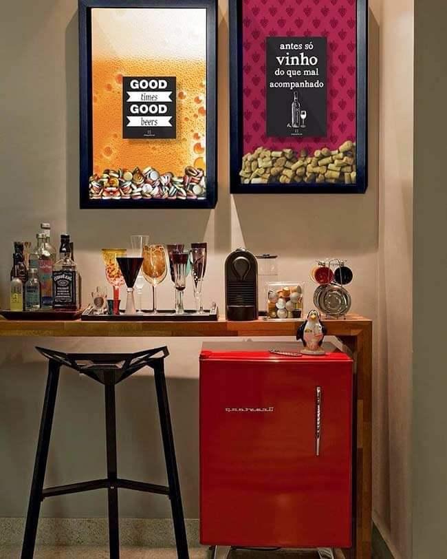aparador servindo de apoio para bebidas e taças. 2 quadros na parede e um frigobar vermelho