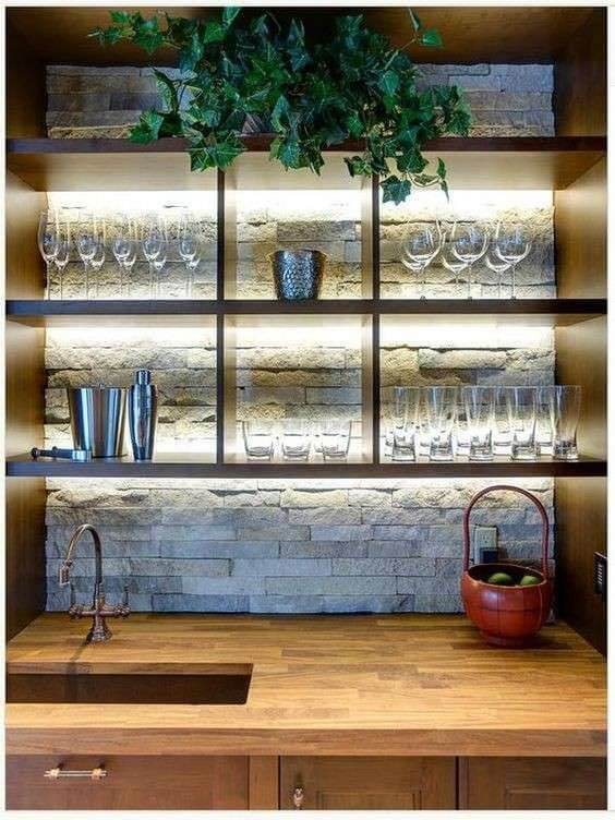 bar de parede com prateleiras luz, taças e folhagens.