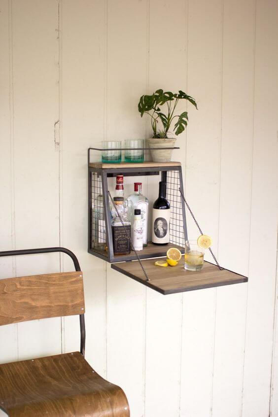 cadeira antiga de madeira e ferro e suporte de parede de ferro com bebidas e copos