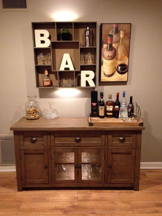 nicho de parede com copos quadro de vinhos e balcao de madeira