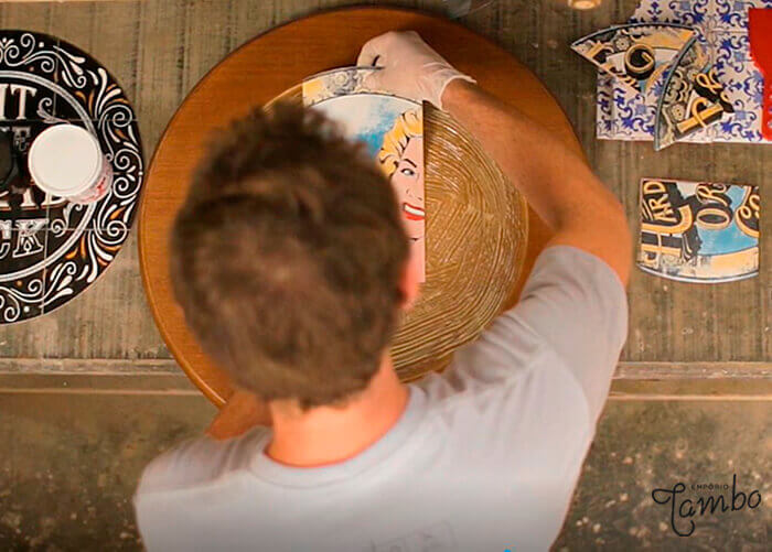 Pessoa colando azulejo em um madeira redonda.