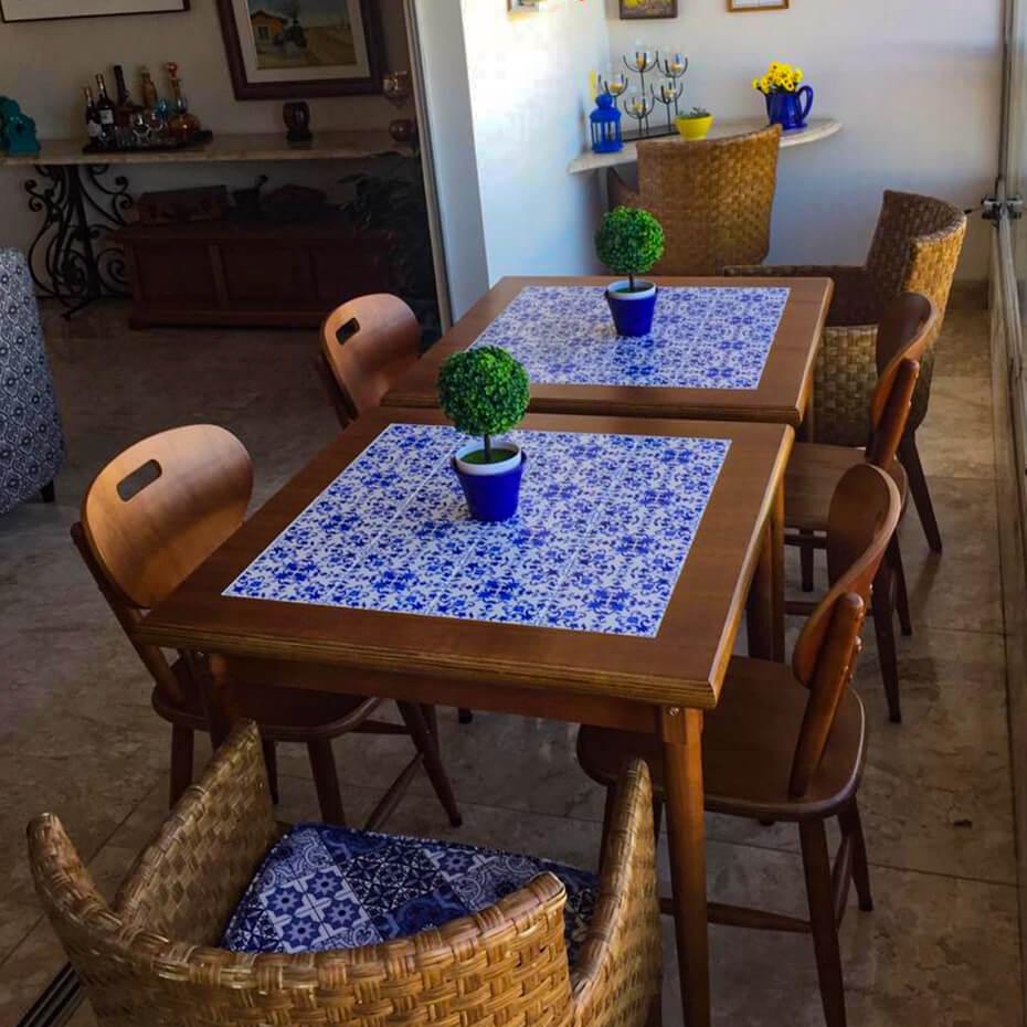 Mesas com estampa de ladrilho português, cadeiras de madeira.