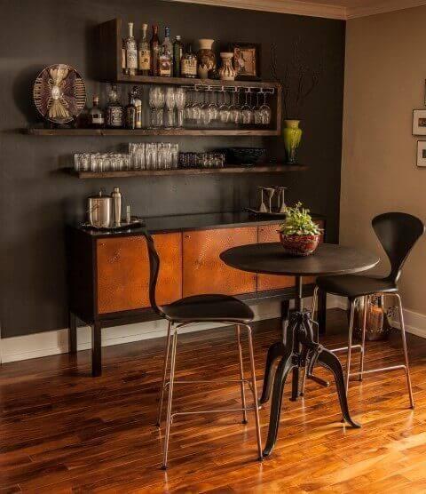 sala com chão de madeira parede preta com prateleiras de madeira de demolição