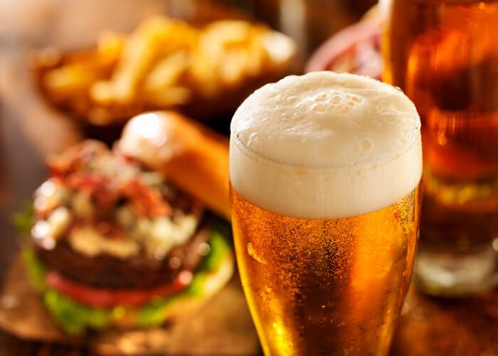 copo de cerveja em primeiro plano com hamburguer desfocado
