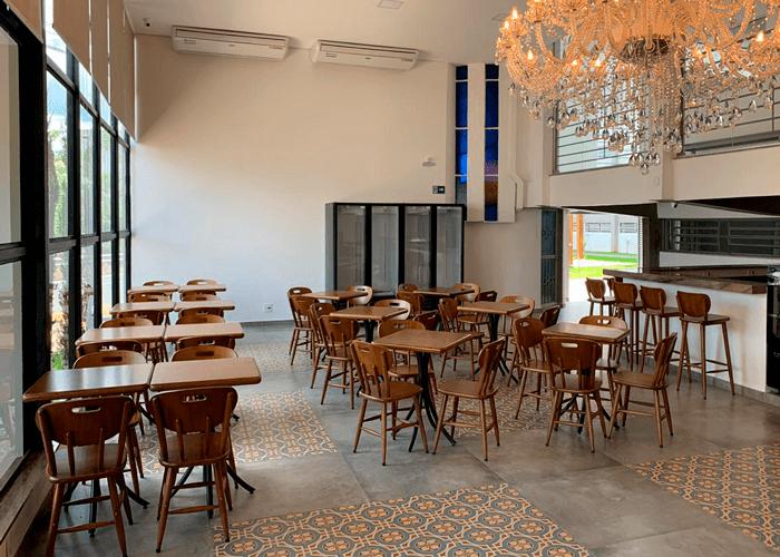 Cafeteria com vários conjuntos de mesas e cadeiras em madeira. Um grande lustre se destaca.