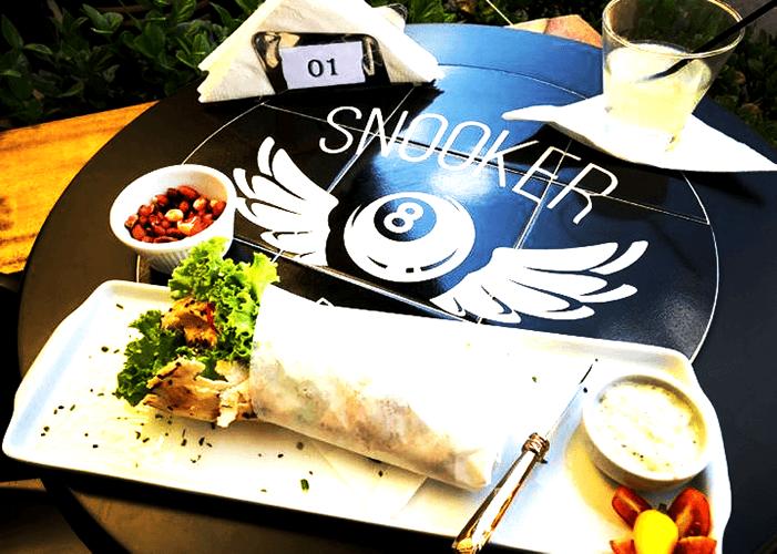 Detalhe de comida em cima de mesa preta com estampa no azulejo