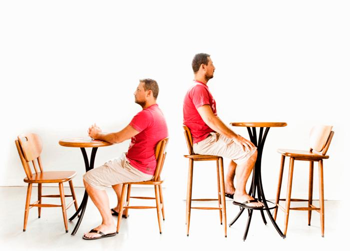 Pessoa sentada na cadeira apoiada em mesa baixa e outra sentada em banqueta em mesa alta.