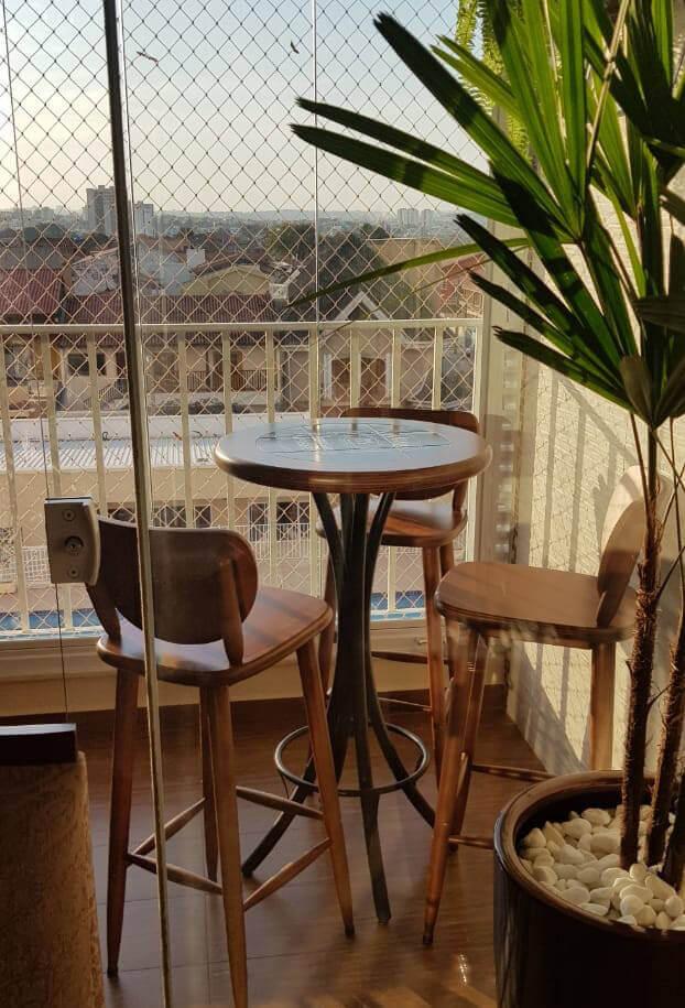 mesa alta com banquetas em uma varanda pequena com uma árvore artificial