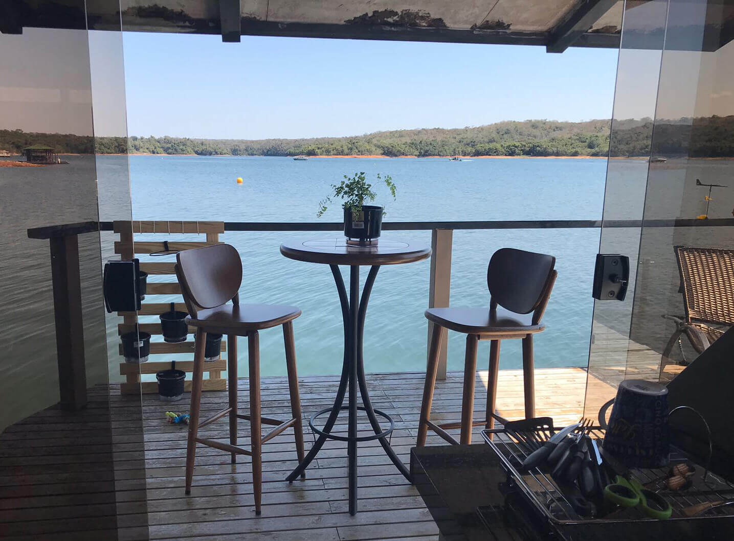 mesa redonda alta com banquetas em deck de madeira com visão para o rio (2)