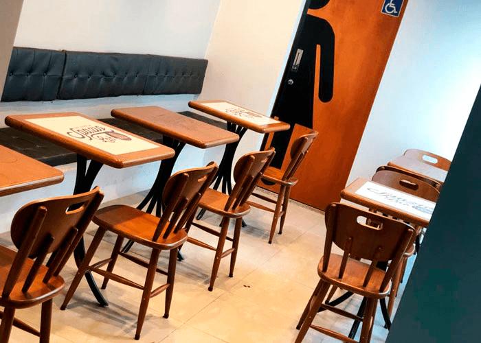 Mesas quadradas de madeira com várias cadeiras em ambiente interno.