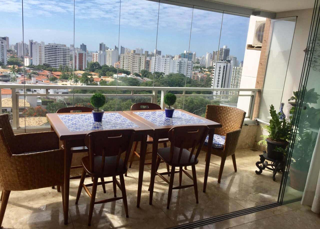 varanda fechada com vidro e duas mesas quadradas baixas com cadeiras